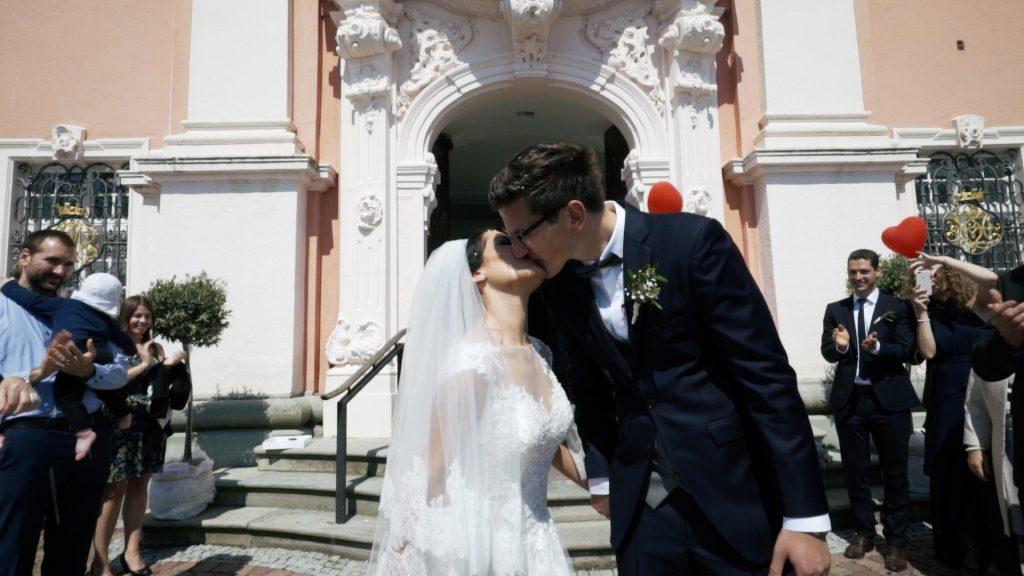 Kuss vor der Kirche nach der Hochzeit
